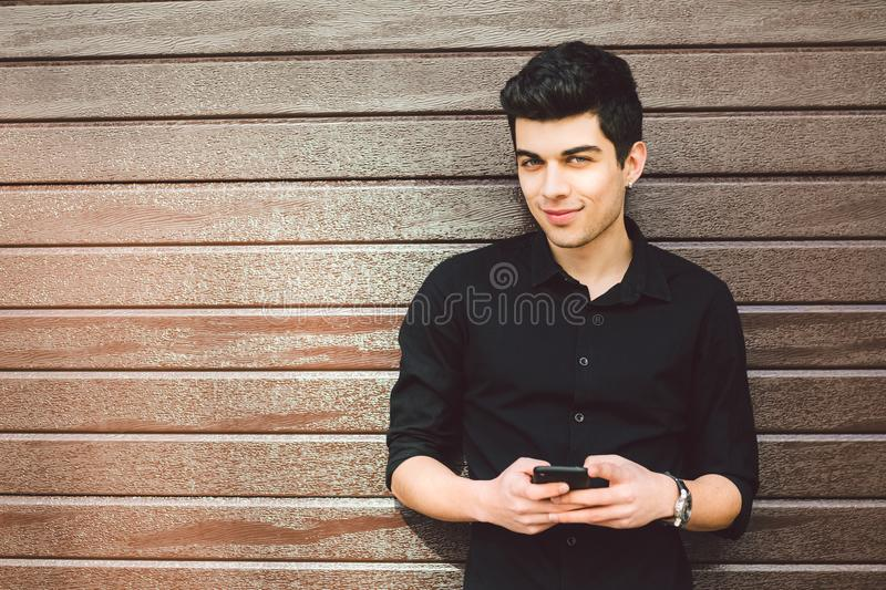 Portrait of young handsome Turkish male model. Mediterranean race brunette in black shirt is using a hand phone of a royalty free stock photos