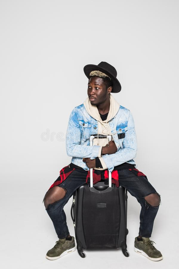 Portrait of young happy african man sitting on suitcase isolated on white background royalty free stock photos