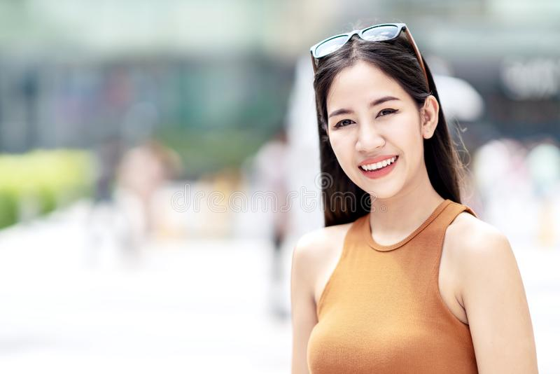 Portrait of young happy attractive asian woman smiling to camera at city background in concept of beauty skin care uv sun screen stock image