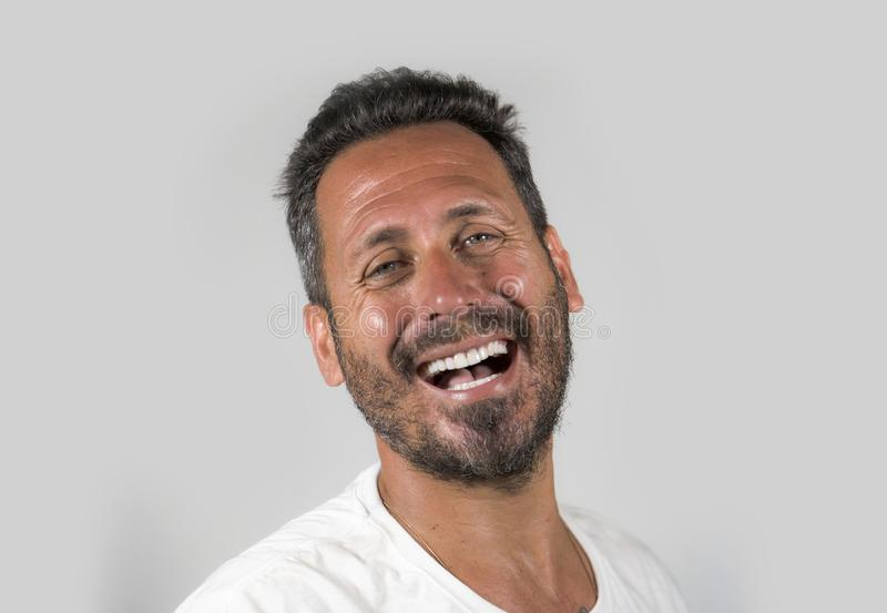 Portrait of young happy and attractive man with blue eyes and beard looking cool smiling happy and confident wearing white t-shirt stock photo