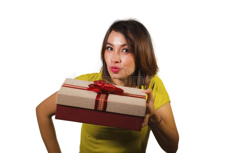 Portrait of young happy and beautiful Asian Indonesian woman giving or receiving Christmas present or birthday gift box with red royalty free stock photography