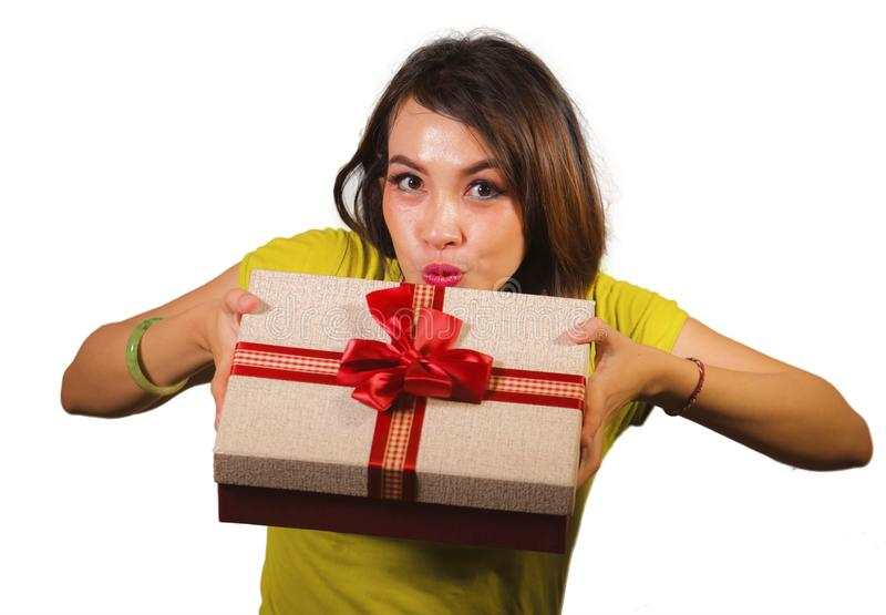Portrait of young happy and beautiful Asian Indonesian woman giving or receiving Christmas present or birthday gift box with red stock photo