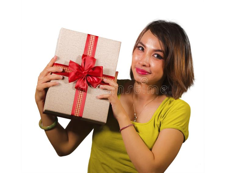 Portrait of young happy and beautiful Asian Indonesian woman holding Christmas present or birthday gift box with red ribbon royalty free stock photos