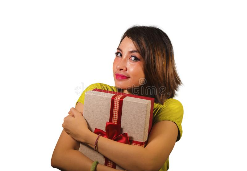 Portrait of young happy and beautiful Asian Indonesian woman holding Christmas present or birthday gift box with red ribbon royalty free stock images