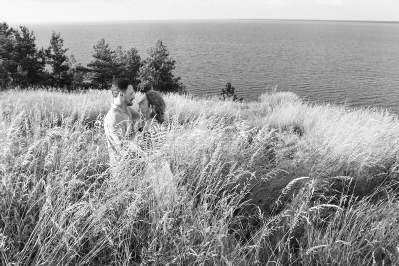 Portrait of young happy beautiful couple on nature with big lake. Young couple hugging on bank of river or sea royalty free stock photos