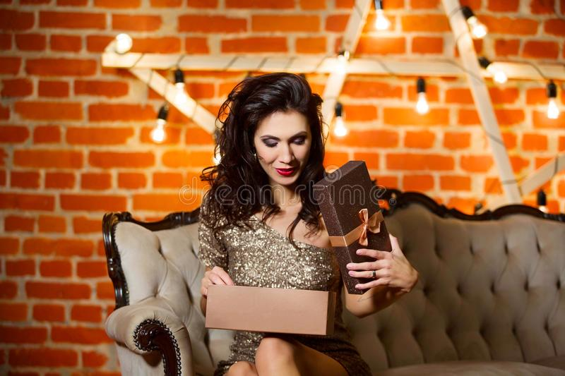 Portrait of young happy beautiful woman in golden dress holding stock photo
