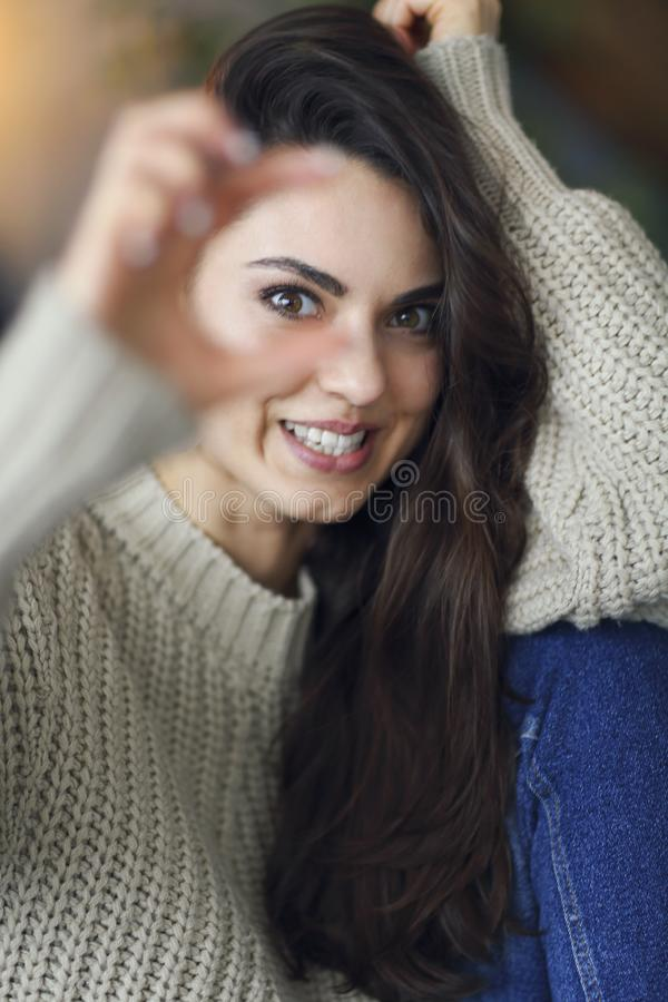 Portrait of a young happy beautiful woman in warm clothings at home stock images