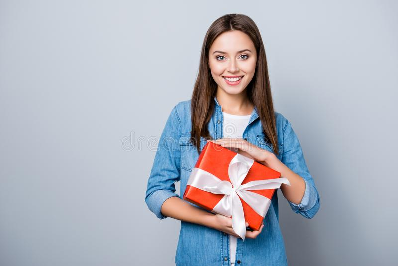 Portrait of young, happy birthday girl, holding a present in red stock photography