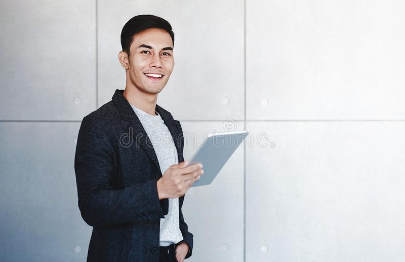 Portrait of Young Happy Businessman Using Digital Tablet. Standing by the Industrial Concrete Wall stock photo