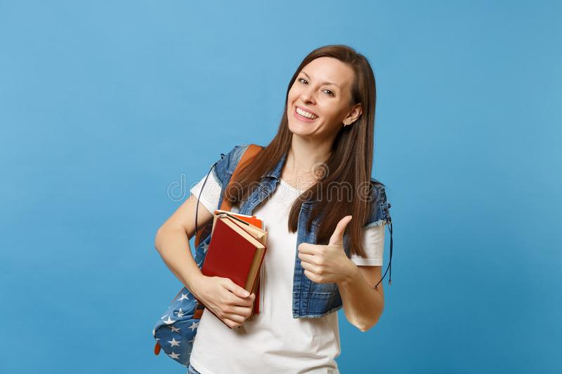 Portrait of young happy charming woman student with backpack showing thumb up, holding school books, ready to learning. Isolated on blue background. Education stock photos
