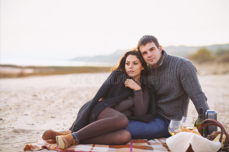 Portrait of young happy couple in a cold day by the autumn sea stock photo