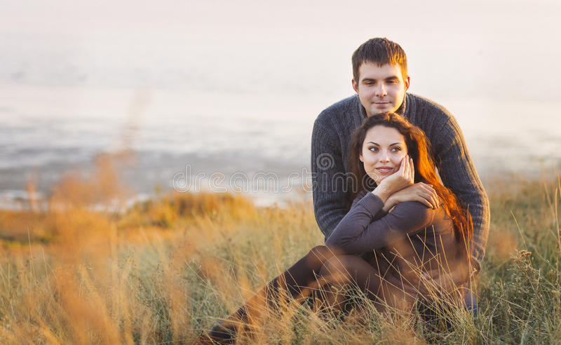 Portrait of young happy couple laughing in a cold day by the autumn sea stock images