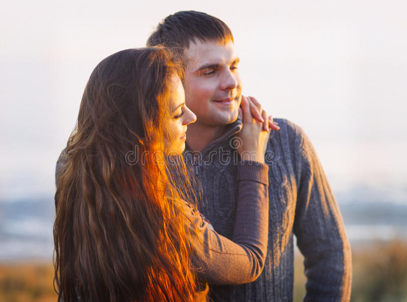 Portrait of young happy couple laughing in a cold day by the autumn sea royalty free stock photo