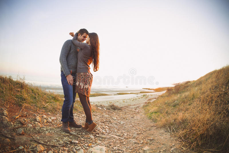 Portrait of young happy couple laughing in a cold day by the sea stock image