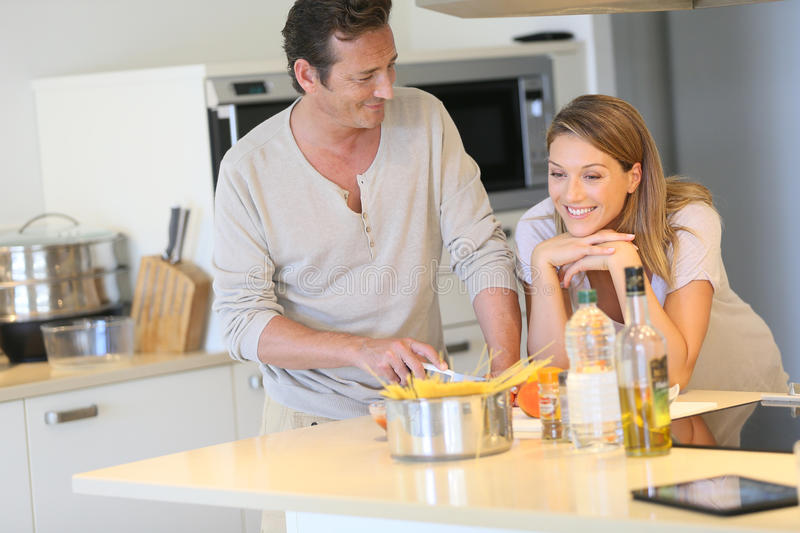 Portrait of a young happy couple preparing a meal in the kitchen royalty free stock photography