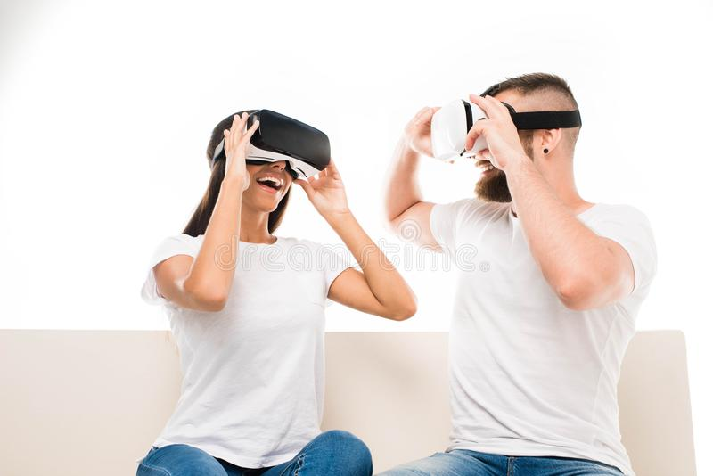 Portrait of young happy couple sitting on sofa using virtual reality headsets, stock photos