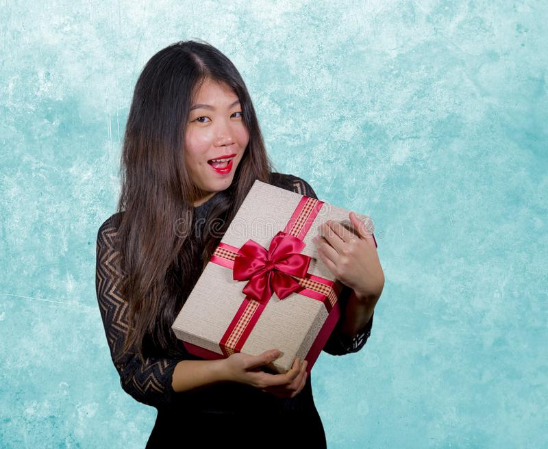 portrait of young happy and excited beautiful Asian Japanese woman receiving a romantic anniversary gift box holding the royalty free stock image
