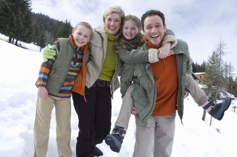 Portrait of young happy family standing in snow stock photo