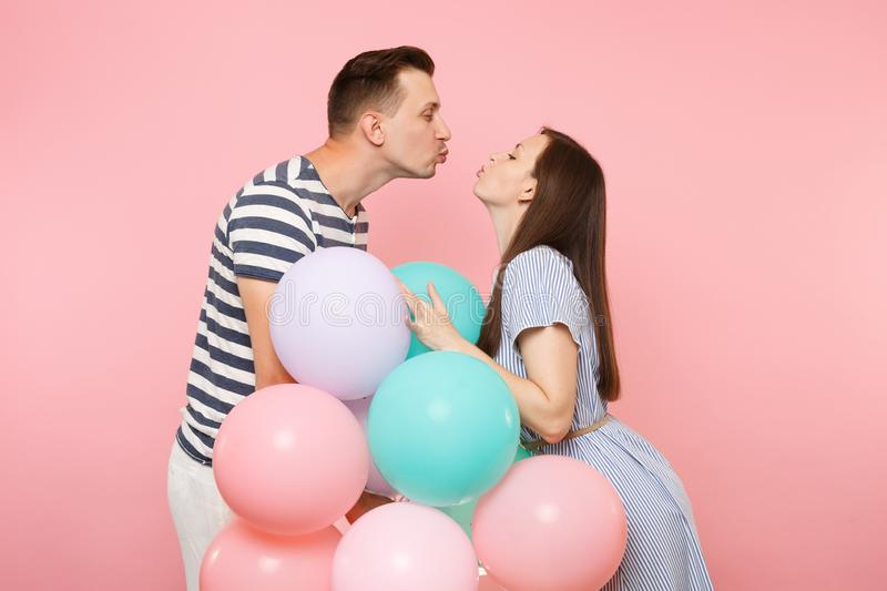 Portrait of young happy kissing couple in love. Woman and man in blue clothes celebrating birthday holiday party on stock photography