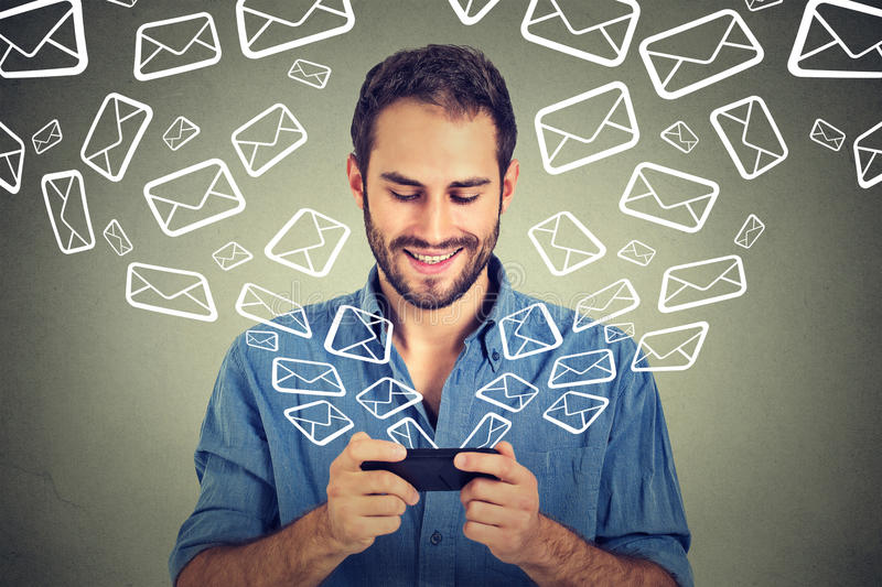 Portrait young happy man busy sending messages emails from smart phone royalty free stock photo