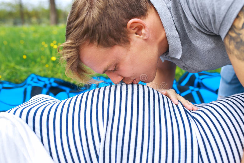 Portrait of young happy man kissing belly of his pregnant woman wife royalty free stock image