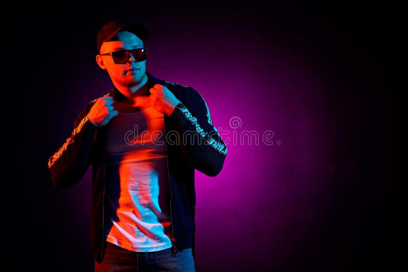 Portrait of a young happy serious man at studio. High Fashion male model in colorful bright neon lights posing on black stock photos