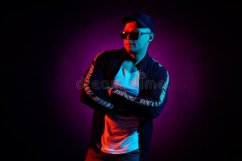 Portrait of a young happy serious man at studio. High Fashion male model in colorful bright neon lights posing on black stock photography