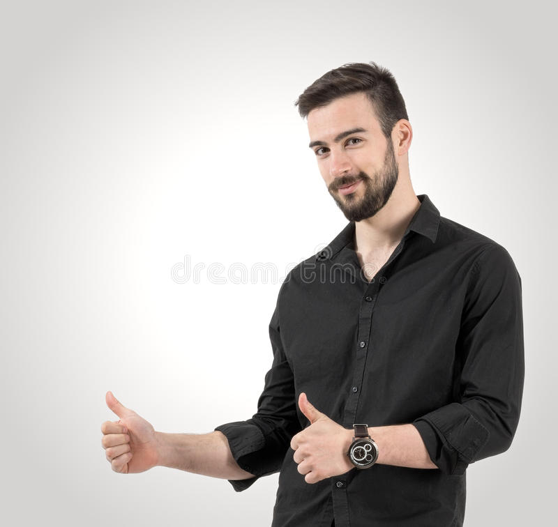 Portrait of young happy smiling man with thumbs up gesture. Desaturated over retro vignette studio background royalty free stock photo