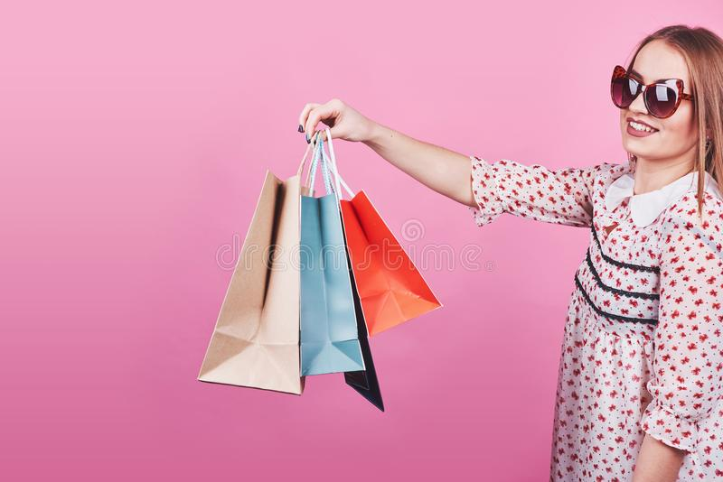 Portrait of young happy smiling woman with shopping bags on the pink Background royalty free stock photography