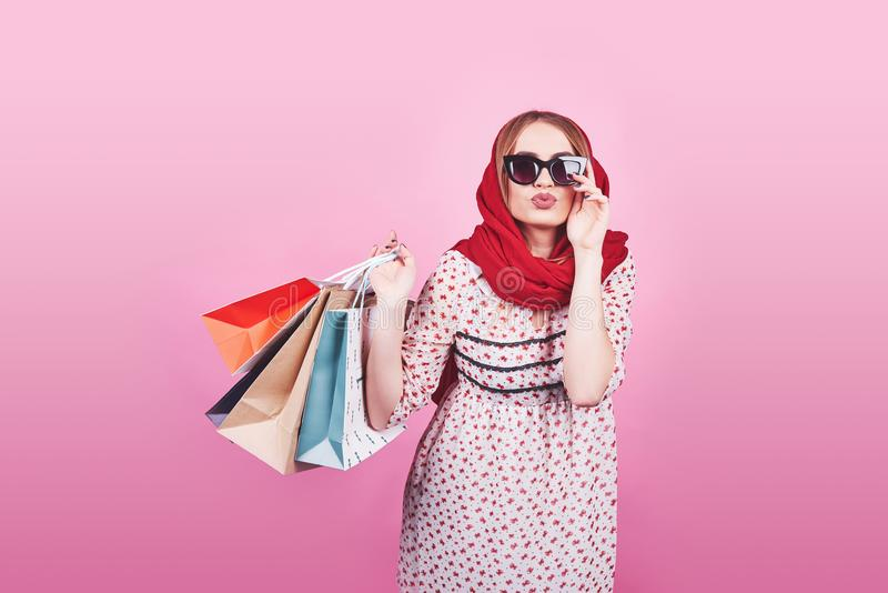 Portrait of young happy smiling woman with shopping bags on the pink Background royalty free stock photos