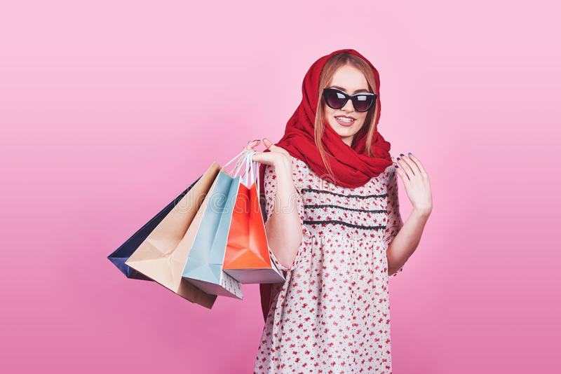 Portrait of young happy smiling woman with shopping bags on the pink Background stock photos