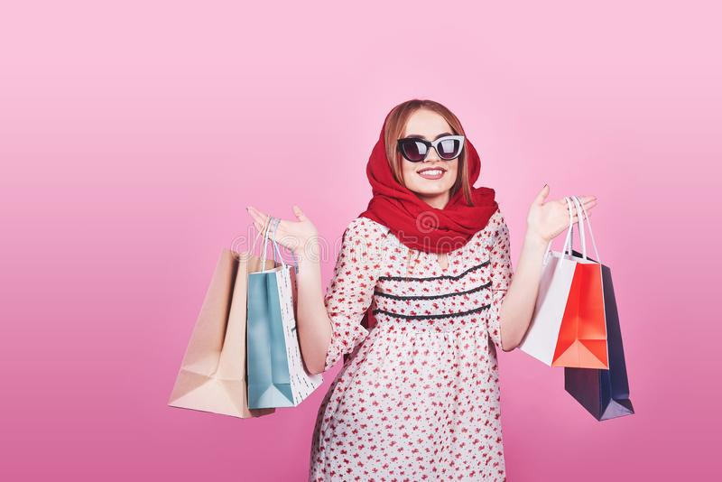 Portrait of young happy smiling woman with shopping bags on the pink Background stock photo