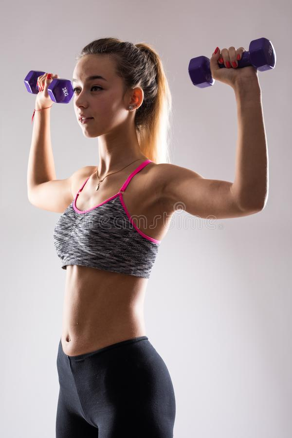 Portrait of young happy smiling woman in sportswear, doing fitness exercise with dumbbell over white background stock images