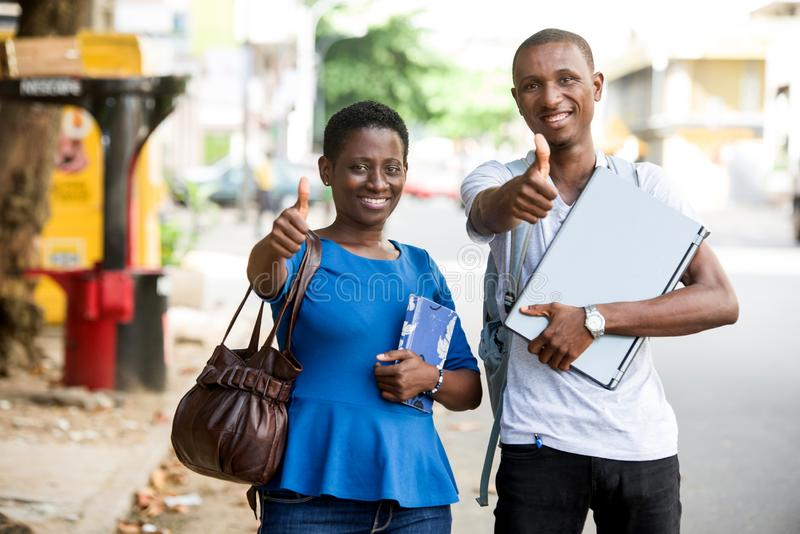 Portrait of young happy students outdoors. Young happy students with books and computer outdoors. Young couple is showing thumbs up and good luck. Smart young royalty free stock images