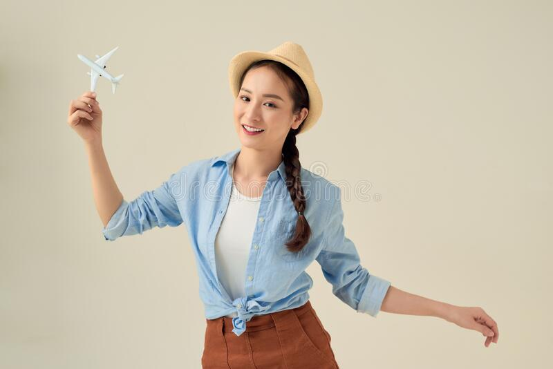 Portrait of young happy woman holding jet aircraft on white background. Advertisement banner for transport companies.  stock photos