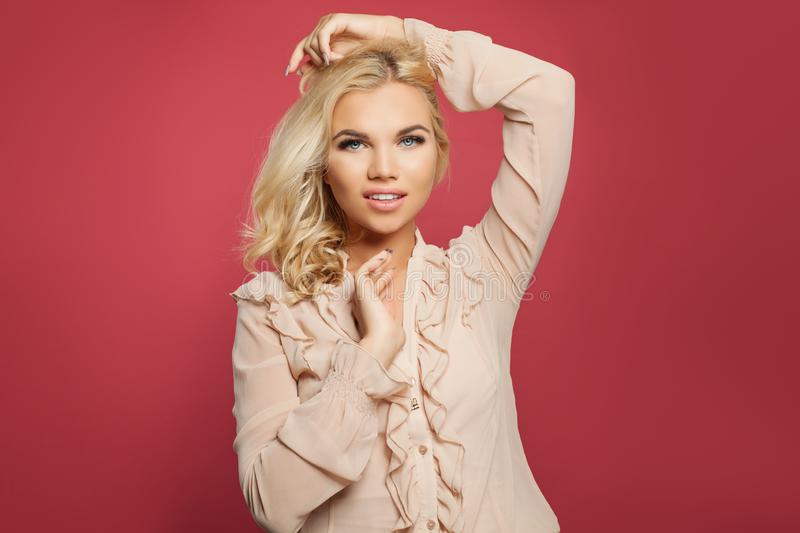 Portrait of young happy woman posing on colorful bright pink background. Blonde girl with blond curly bob hairstyle stock images