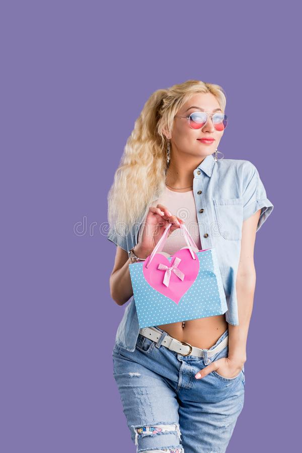 Portrait of young happy woman with shopping bag  over violet background stock image