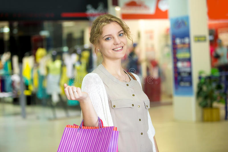 Portrait of young happy woman in shopping center royalty free stock photo
