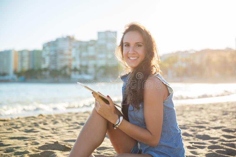 Young happy woman sitting on beach holding tablet royalty free stock image
