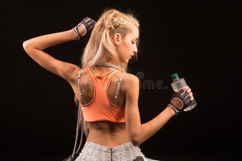 Portrait of young and healthy blonde with skipping rope and bottle of water. Over the black background stock photo
