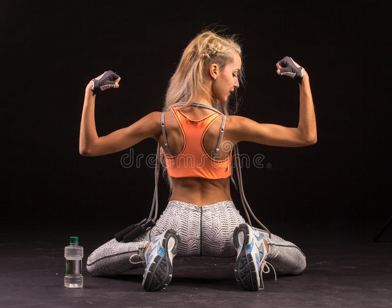 Portrait of young and healthy blonde with skipping rope and bottle of water. Young and healthy blonde sitting on her knees with skipping rope and bottle of water royalty free stock photography