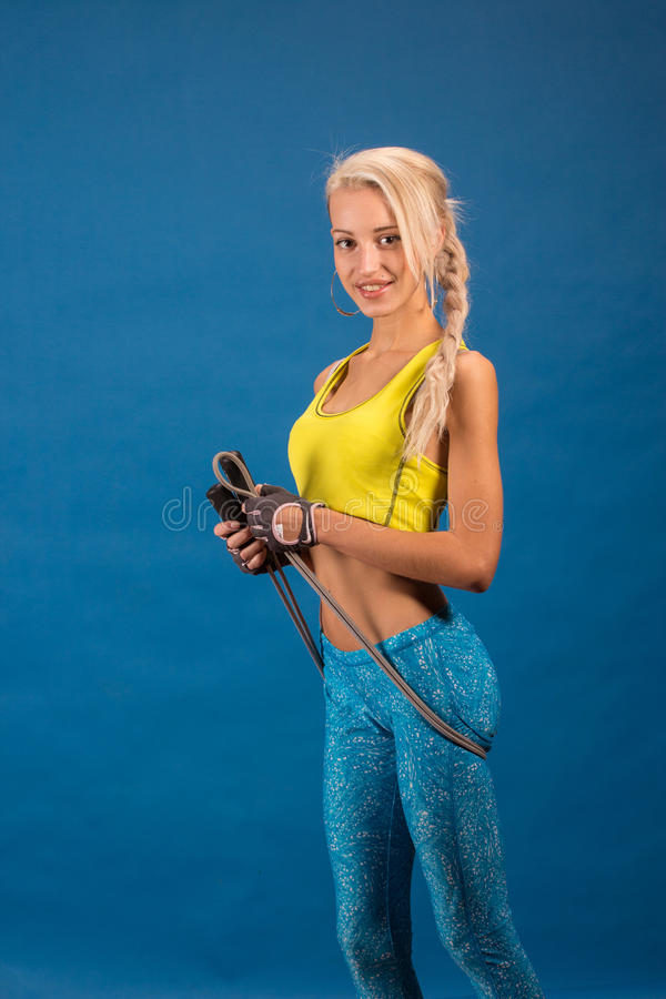 Portrait of young and healthy blonde with skipping rope. Over the blue background stock photos