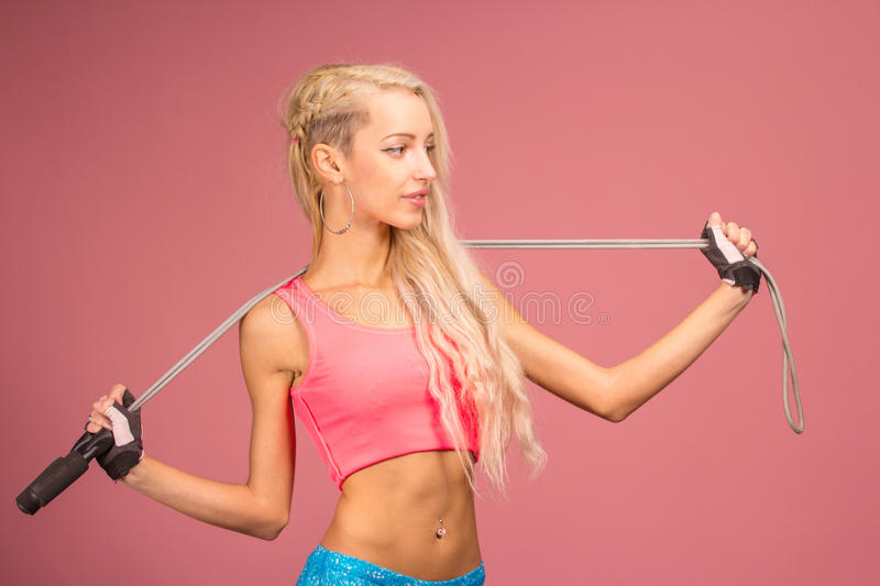 Portrait of young and healthy blonde with skipping rope. Over the yellow background royalty free stock photo