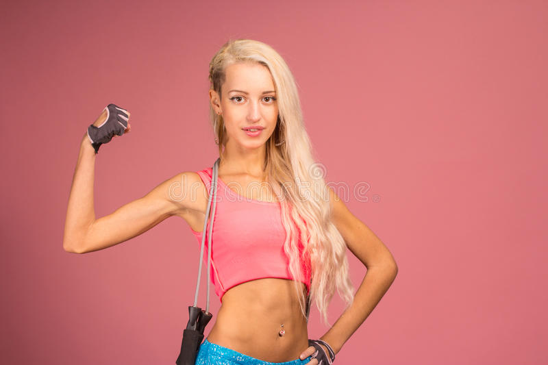 Portrait of young and healthy blonde with skipping rope. Over the yellow background stock photo