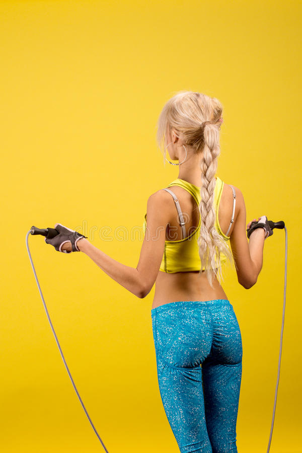 Portrait of young and healthy blonde with skipping rope. Over the yellow background. Back view stock photography