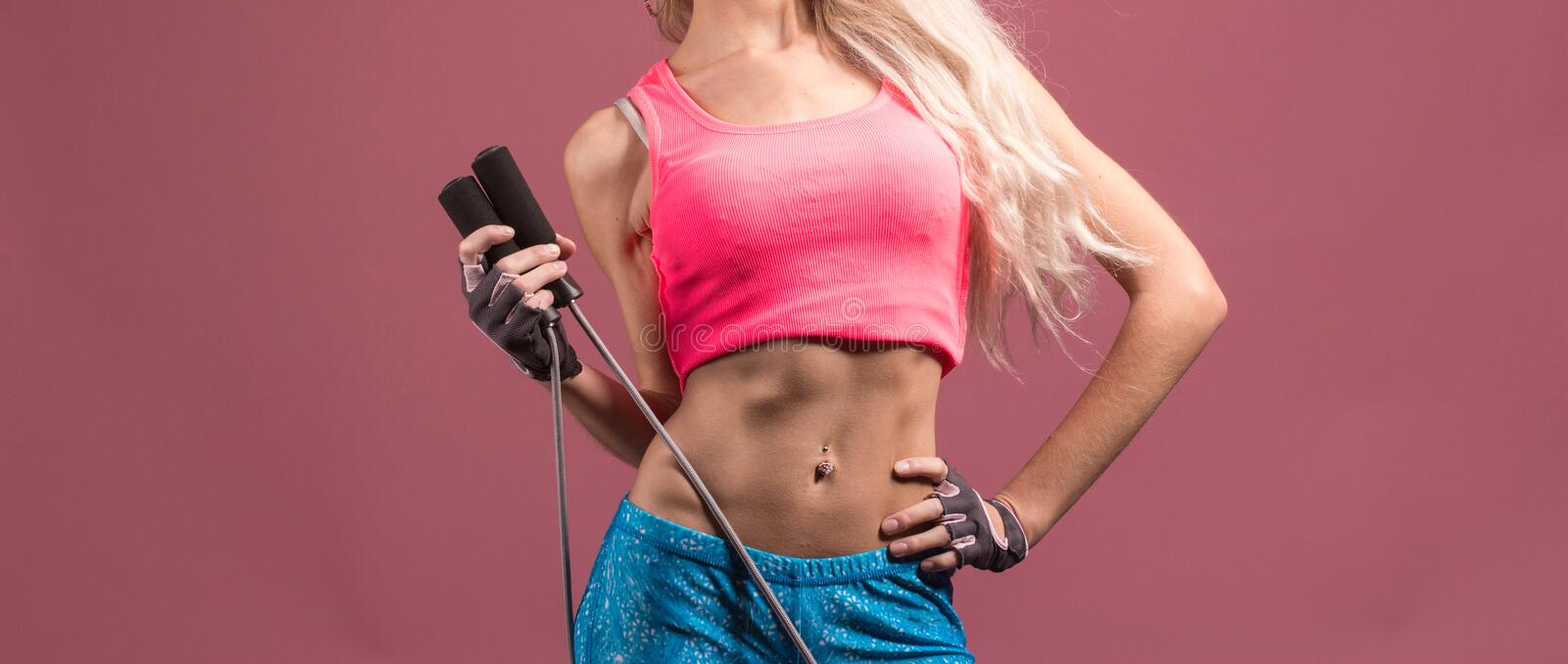 Portrait of young and healthy blonde with skipping rope. On the pink background stock photography