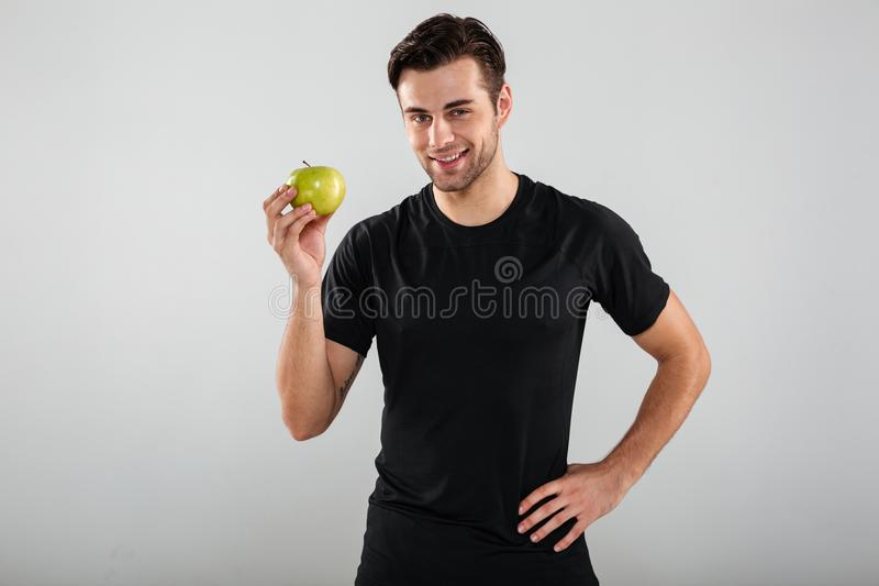 Portrait of a young healthy man holding green apple stock image
