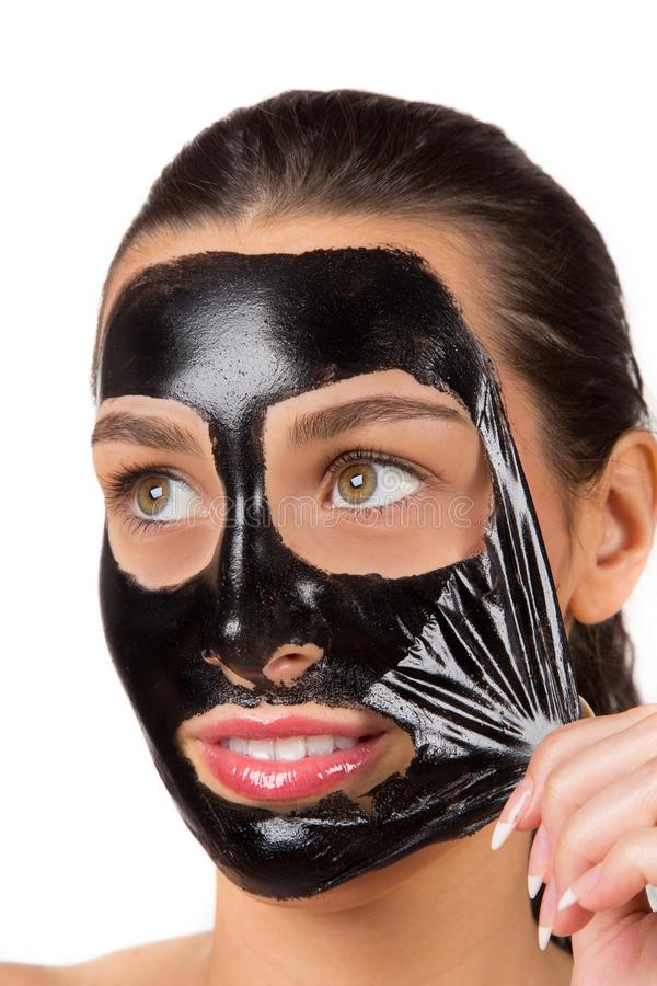 Portrait of young healthy woman with black peel face mask. stock images