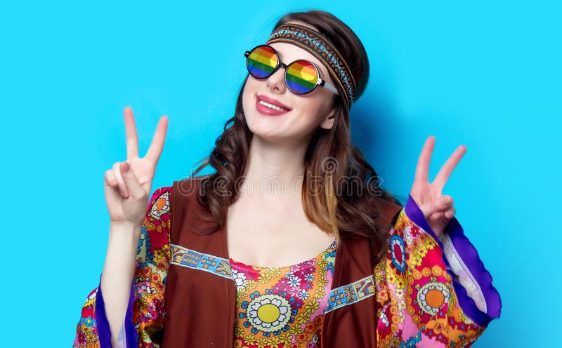 Portrait of Young hippie girl with rainbow glasses. On blue background stock images