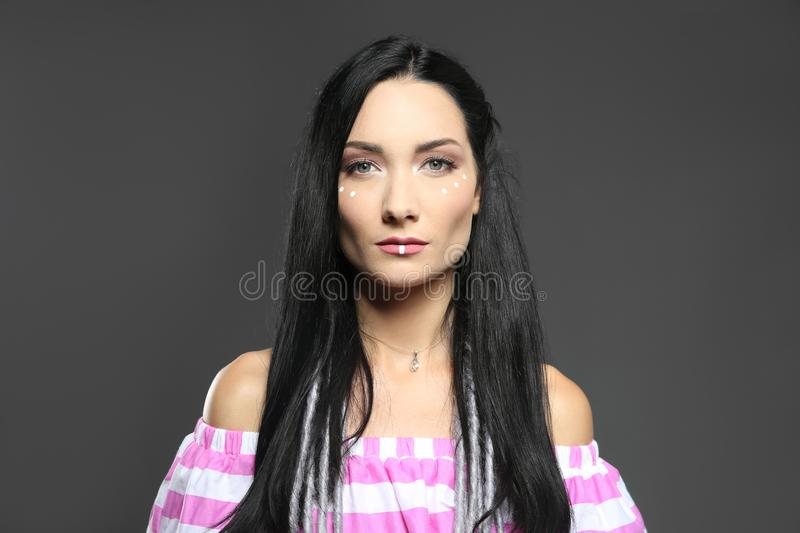 Portrait of young hippie woman with boho makeup in stylish outfit on grey background royalty free stock images